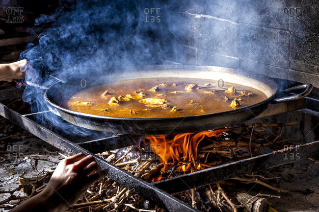 Crop unrecognizable hands holding big iron pan with boiling broth for cooking paella over open fire with wood