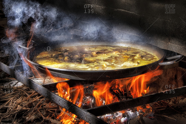 Big iron pan with boiling broth for cooking paella over open fire with wood