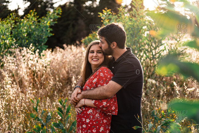 Pensive man hugging tenderly smiling pregnant wife on background of picturesque green park in sunny day