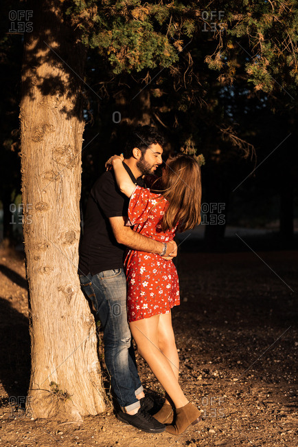 Man hugging tenderly smiling pregnant wife on background of picturesque green park while leaning in a tree in sunny day
