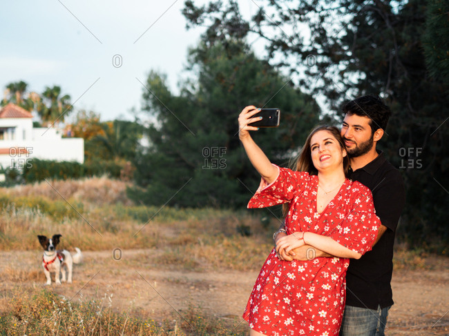 Happy young couple kissing and taking selfie while during walking with small dog in summer park