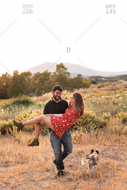 Cheerful couple playing while man his caring woman among yellow grass of countryside in summer day