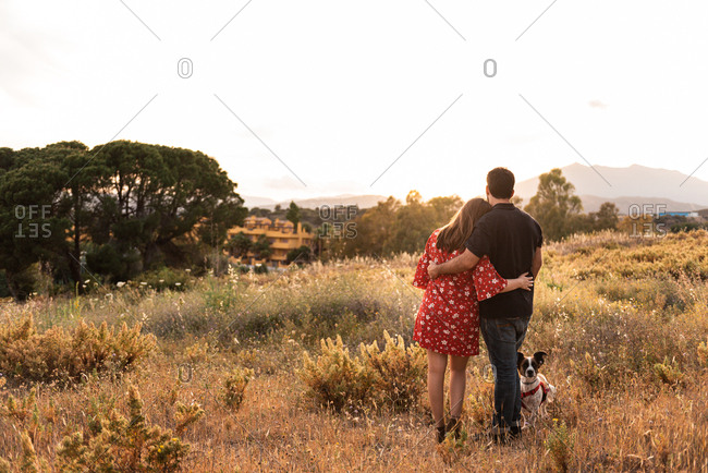 Back view of unrecognizable couple having fun with a little dog among high grass in countryside while admiring the views