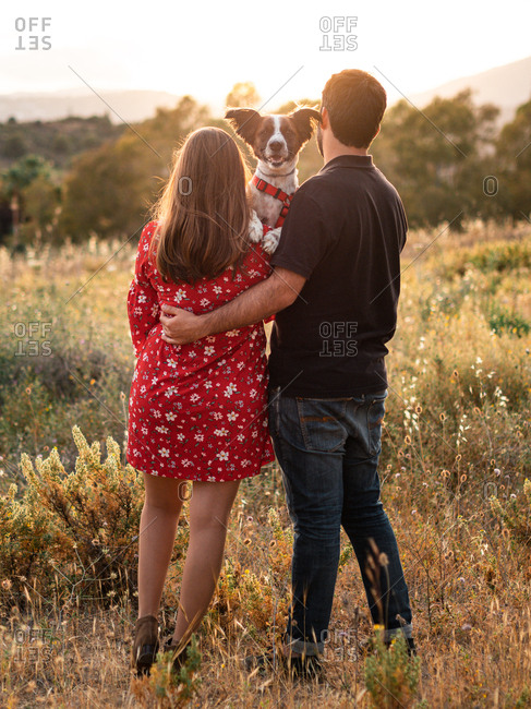 Back view of unrecognizable couple having fun and holding up a little dog among high grass in countryside while admiring the views