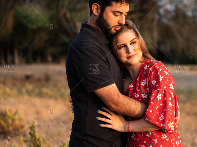 Man hugging tenderly smiling pregnant wife on background of picturesque green park in sunny day