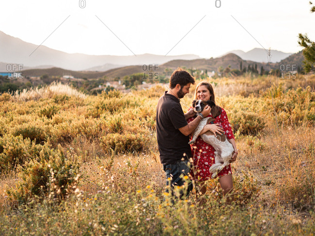 Smiling cheerful couple having fun and holding up a little dog among high grass in countryside