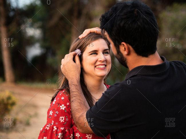 Man tenderly smiling at wife while putting a flower behind her ear on background of picturesque green park in sunny day