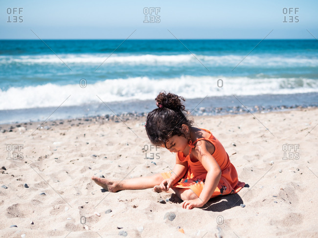 Back view of female kid in orange dress sitting on sandy seaside and playing