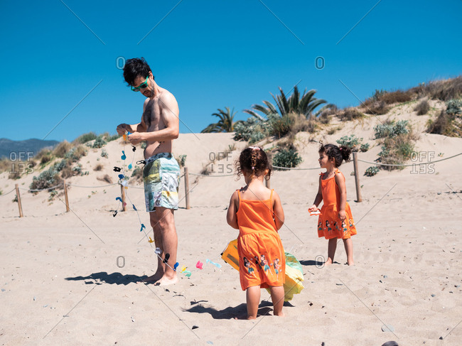 Father and twins in bright orange dresses playing with flying kite on sandy seaside in sunny day