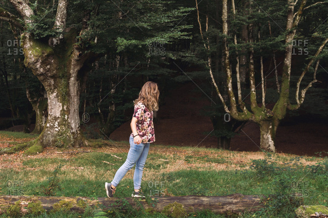 Side view of young female tourist with long hair walking on log along dark old mystique forest