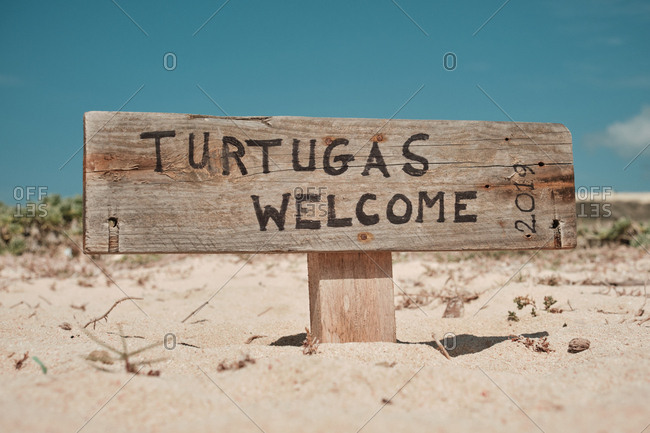 Old wooden road sign Turtugas welcome in hot dry dessert