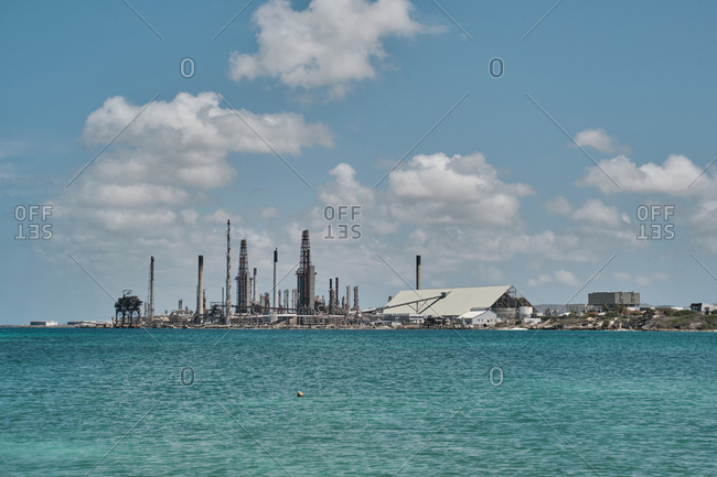 Serene turquoise waves and industrial port with working buildings waiting for ships and boats in bright cloudy day