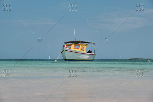 Amazing white and yellow boat on serene waves ready for sailing in bright day