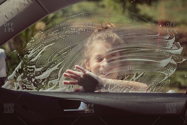 Smiling kid having fun with foam washing front glass of car by hand
