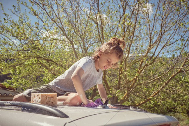 Adorable happy energetic child with cleaning tools sitting on foamy glass roof of car while washing