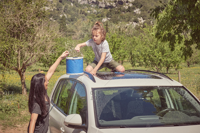 Side view of hardworking child watering roof of car from blue bucket and woman squeezing sponge