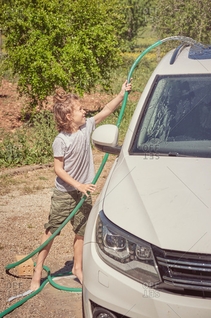 Side view of cheerful child washing grey car with hose in bright summer day