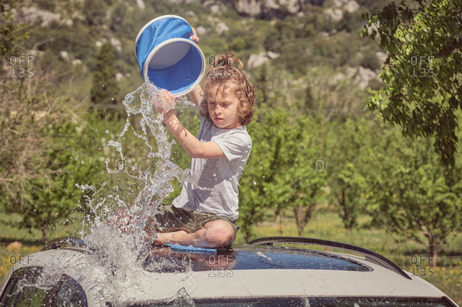 Excited child watering roof of car from blue bucket and washing it with foam sponge