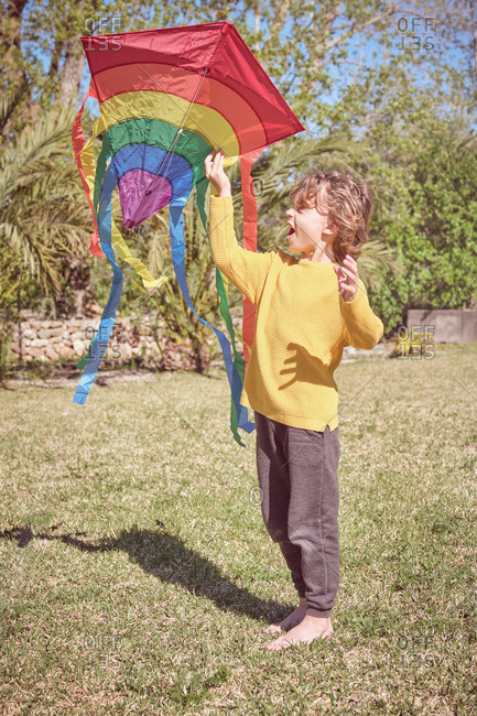 Side view of happy kid playing with colorful kite flying in blue sky on nature background
