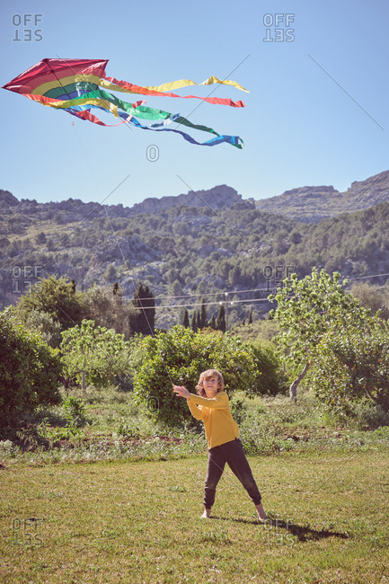 Happy kid playing with colorful kite flying in blue sky on nature background