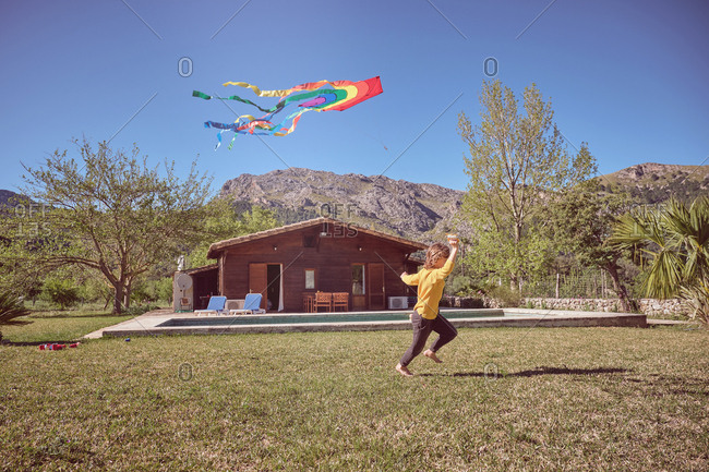 Happy kid playing with colorful kite flying in blue sky near wood cabin on nature background