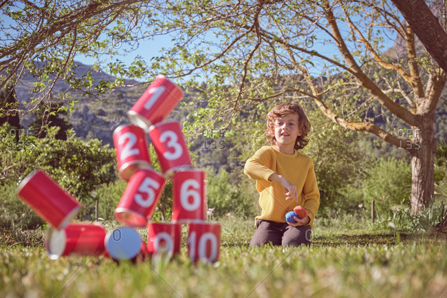 Cheerful kid kneeling and throwing balls in pyramid of red tin cans on nature background