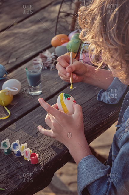 Crop unrecognizable child sitting and painting eggs with bright color at wooden table