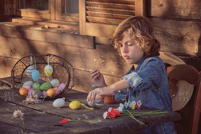 Side view of adorable child sitting and painting eggs with bright color at wooden table