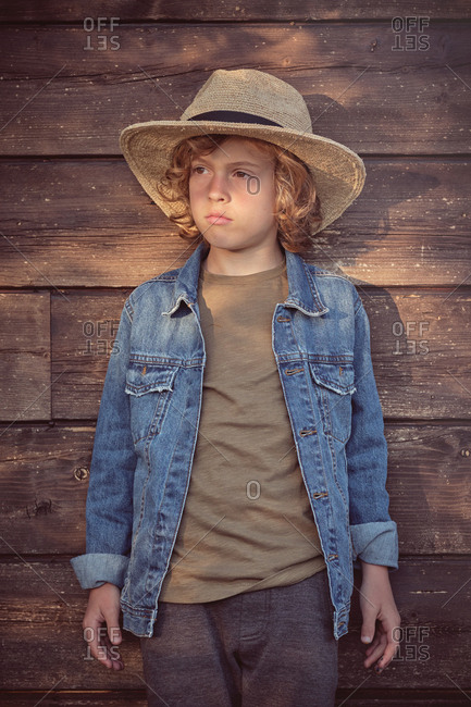 Fashion boy in hat and denim jacket looking away while standing in wooden background