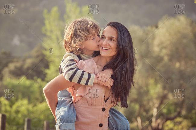 Laughing mom and son having fun doing piggyback on countryside and woman keeping son on back