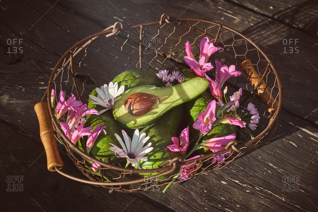 From above tasty ripe avocado with big bone and delicate pink flowers in wicker basket
