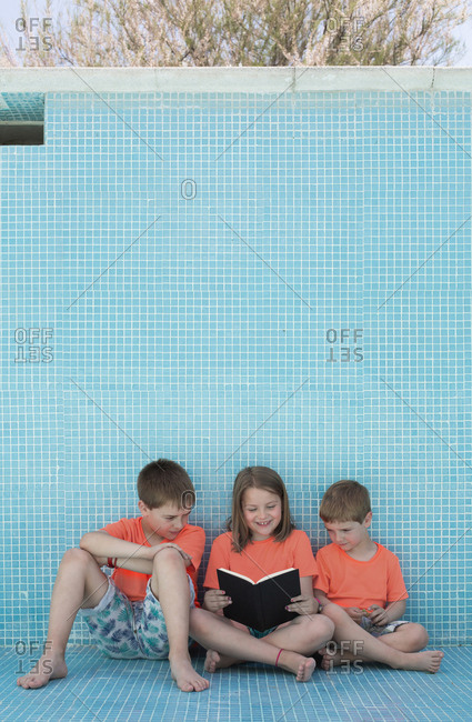 Children sitting in empty pool and reading book