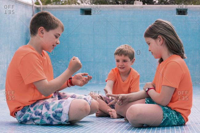 Kids in bright orange T-shirts sitting on bottom of empty pool and playing rock-paper-scissors