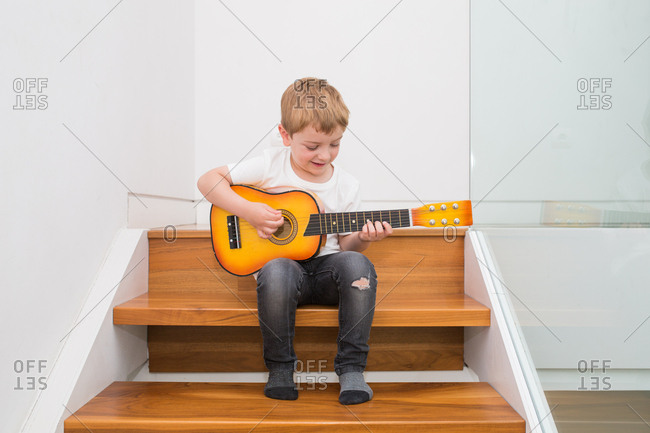 Young blonde boy concentrating while playing guitar