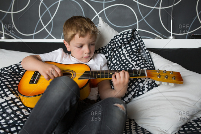 Young blonde boy playing toy guitar