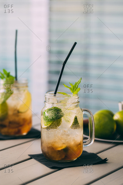 Mojito cocktail prepared with lime, mint, rum, soda and ice in mason jars with natural light, outdoors