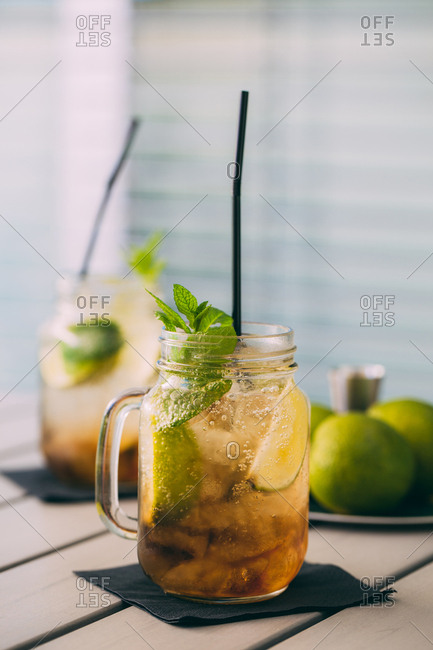 two Mojitos cocktail prepared with lime, mint, rum, soda and ice in mason jars with natural light, outdoors