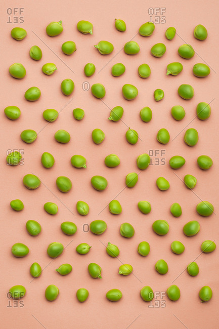 Set of peas placed orderly on salmon colored background