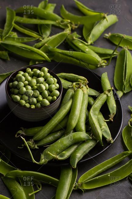 Peeled fresh peas and pea pods on dark background