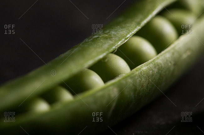 Peeled fresh peas and pea pods on dark background