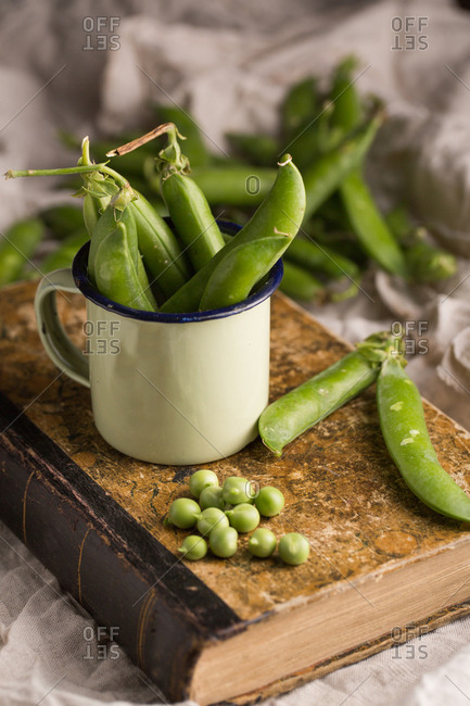 Fresh peas and pea pods in an enamel cup on a grunge background