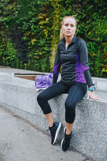 Young blonde caucasian woman with sportswear sitting in a pavement on the street