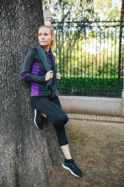Young blonde caucasian woman leaning resting on a tree after doing jogging