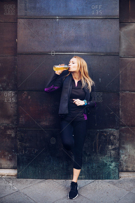 Young blonde caucasian woman drinking isotonic drink while having a rest from a running session leaning in a wall