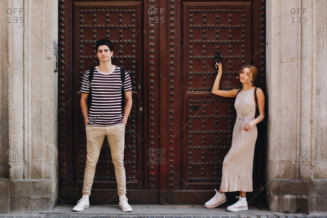 Young cheerful and playful couple in casual clothes posing in front of beautiful old door during dating outdoors