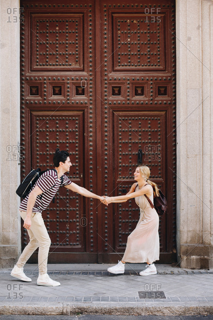 Young cheerful and playful couple in casual clothes having fun during dating outdoors in front of beautiful old door