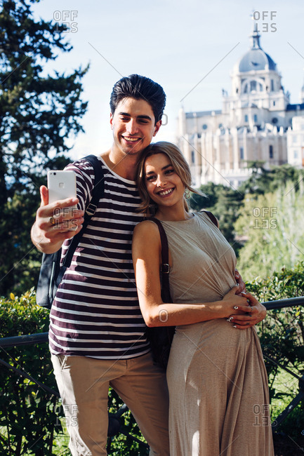 Young handsome man taking photo with girlfriend while walking in beautiful garden on background of historical building