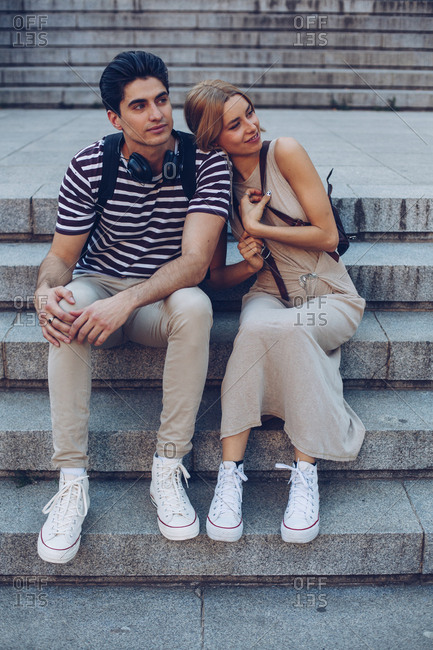 Attractive couple admiring view while sitting on old stairs of historical building