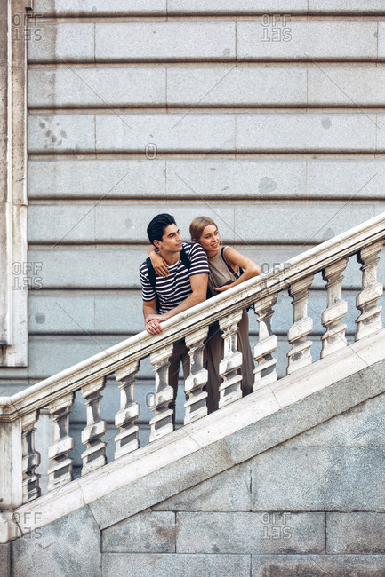 Attractive couple admiring view while standing on old stairs of historical building