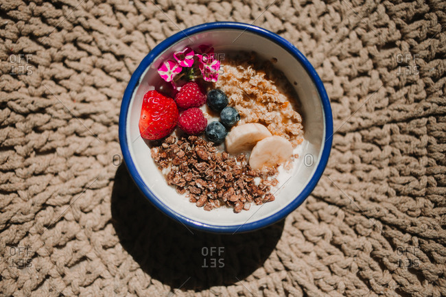 From above appetizing tasty fresh strawberry blueberry banana cereals in bowl